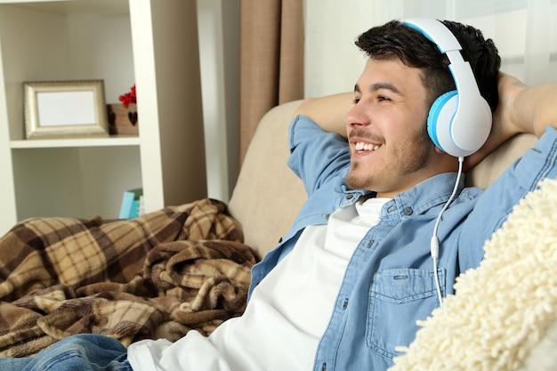 ソファに横になって部屋で音楽を聴いているハンサムな若い男