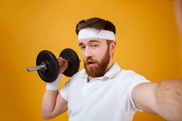 Handsome young man make selfie with dumbbell.