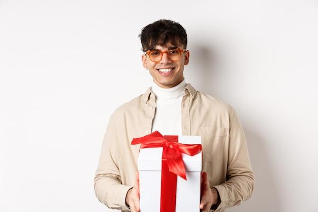 Красивый молодой человек делает подарок, держа коробку с настоящим и улыбается, стоя на белой стене.