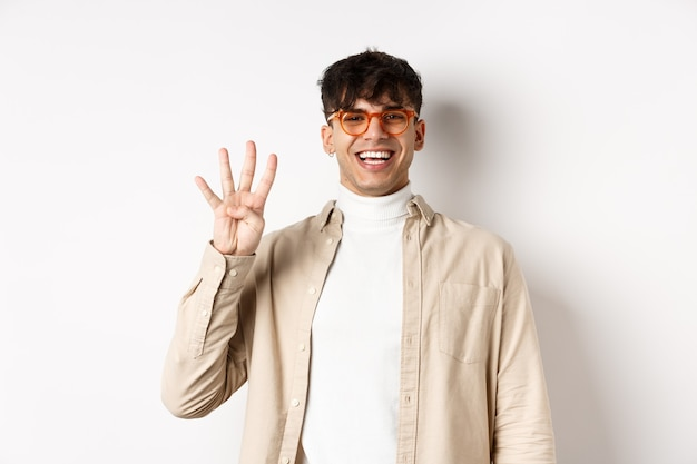 Handsome young man making order, showing number four fingers and smiling, standing on white background.