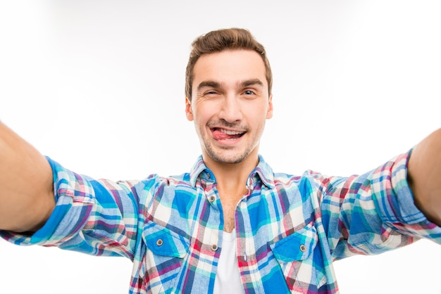 Handsome young man making selfie photo showing tongue