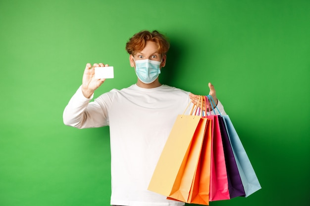 Handsome young man in medical mask, showing plastic credit card and shopping bags with items purchased with discount, green background.