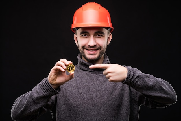 Handsome young man miner in protective hemlet pointed on bitcoin isolated on black