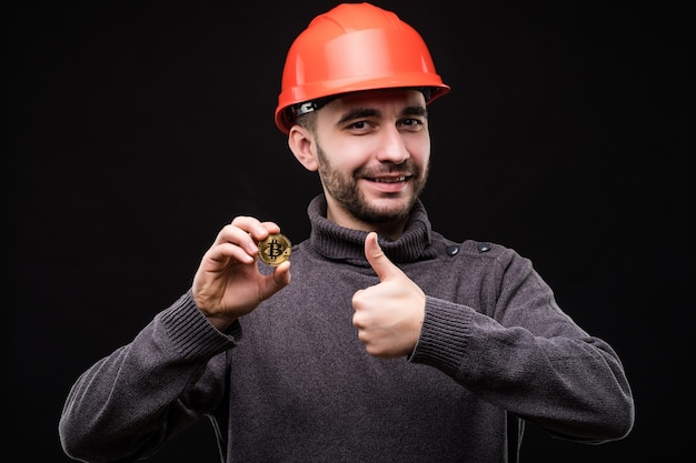 Handsome young man miner in protective hemlet pointed bitcoin with thumbs up isolated on black
