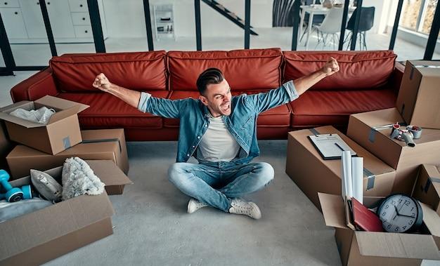 Красивый молодой человек, переезжающий в новый дом среди смеющихся коробок. переезд, покупка дома, концепция квартиры.