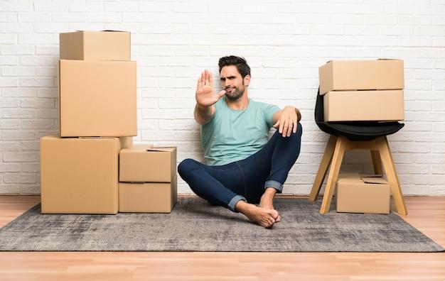 Красивый молодой человек, движущихся в новом доме среди коробок, делая остановки жест рукой