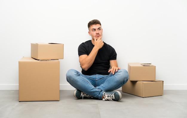 Красивый молодой человек, движущихся в новом доме среди коробок, думая, идея