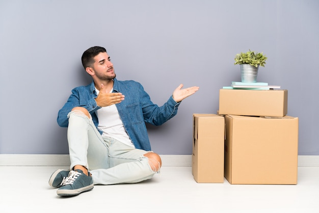 Handsome young man moving in new home among boxes extending hands to the side for inviting to come