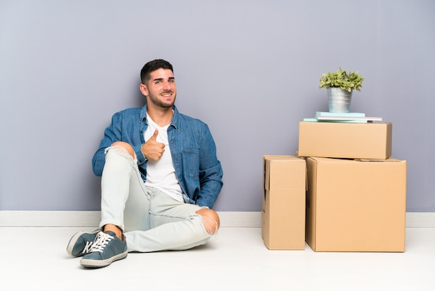 Handsome young man moving in new home among boxes giving a thumbs up gesture