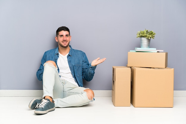 Handsome young man moving in new home among boxes holding copyspace imaginary on the palm
