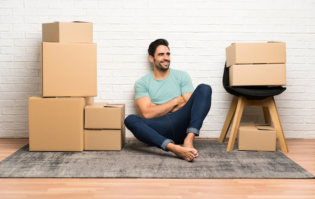 Handsome young man moving in new home among boxes looking to the side