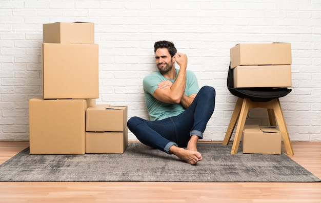 Handsome young man moving in new home among boxes making strong gesture