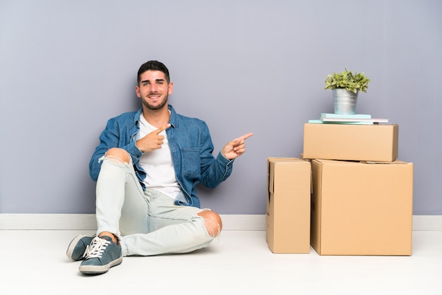 Handsome young man moving in new home among boxes pointing finger to the side