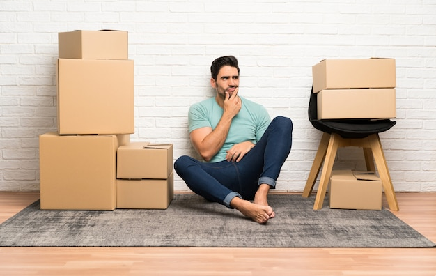 Handsome young man moving in new home among boxes thinking an idea