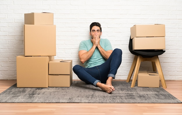 Handsome young man moving in new home among boxes with surprise facial expression