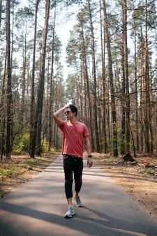 公園を歩いて屋外公園でハンサムな若い男