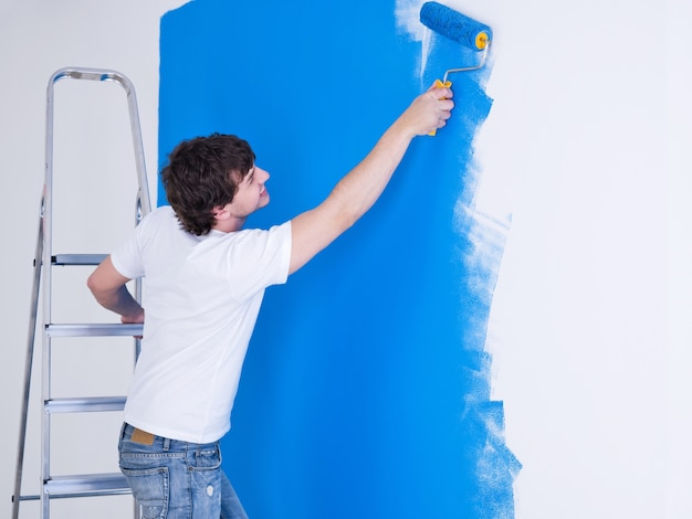 Handsome young man painting the wall in blue
