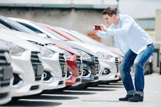 Красивый молодой человек фотографирует автомобили в автосалоне