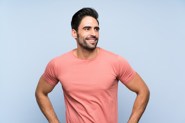 Handsome young man in pink shirt over isolated blue  posing with arms at hip and smiling