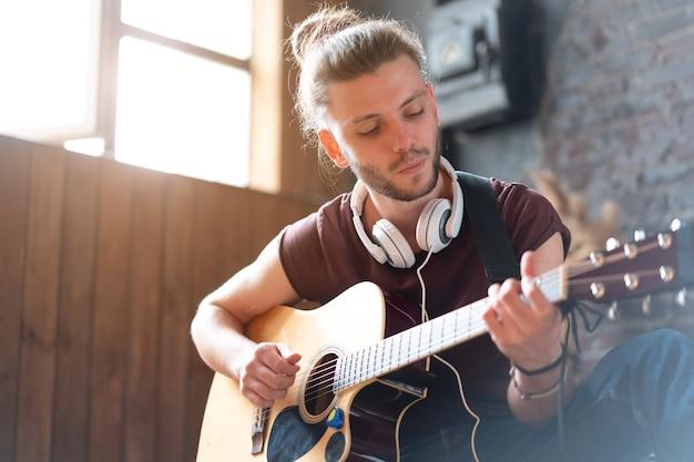 アコースティックギターを演奏するハンサムな若い男座っている床のリビングロフトルーム歌を練習する白人男性のヒップスターヘッドフォンギタープレーヤーは音楽をリラックスして楽しむクリエイティブな現代の若い男ミディアムシュート