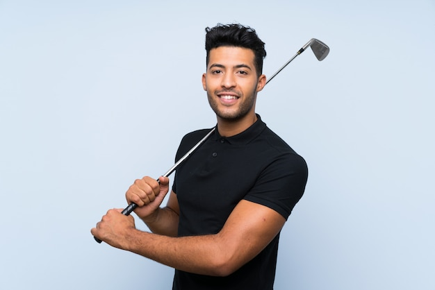 Handsome young man playing golf over isolated blue wall smiling a lot