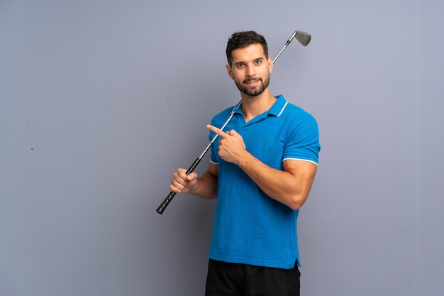 Handsome young man playing golf pointing to the side to present a product