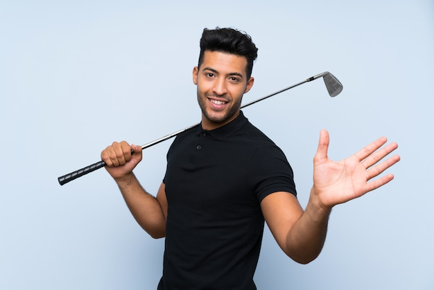 Handsome young man playing golf saluting with hand with happy expression