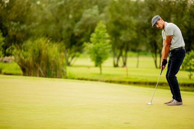 Красивый молодой человек играет в гольф