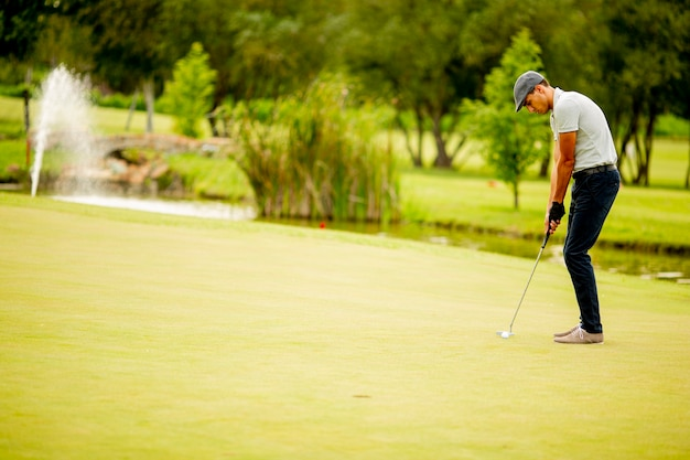 Handsome young man playing golf