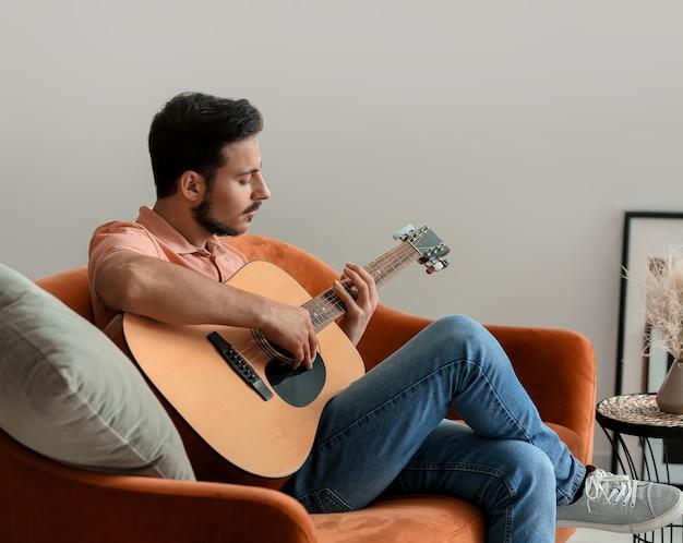 Красивый молодой человек играет на гитаре дома