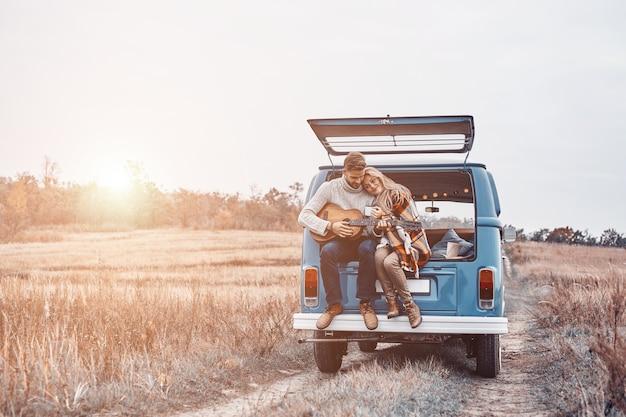 Красивый молодой человек играет на гитаре для своей подруги, сидя в багажнике автомобиля на открытом воздухе