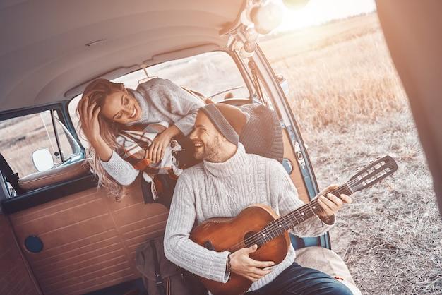 Красивый молодой человек играет на гитаре для своей подруги, проводя время в доме на колесах