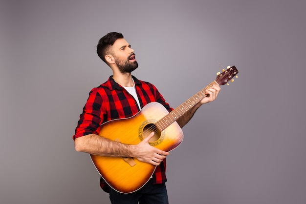 Красивый молодой человек играет на гитаре и поет песню