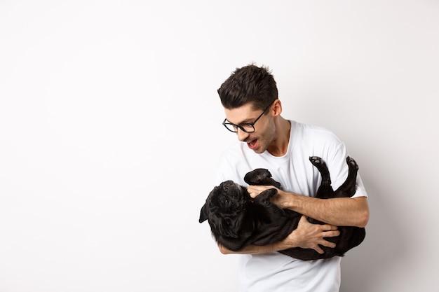 かわいい黒い子犬と遊ぶハンサムな若い男。白の上に立って、パグをかわいがる犬の飼い主