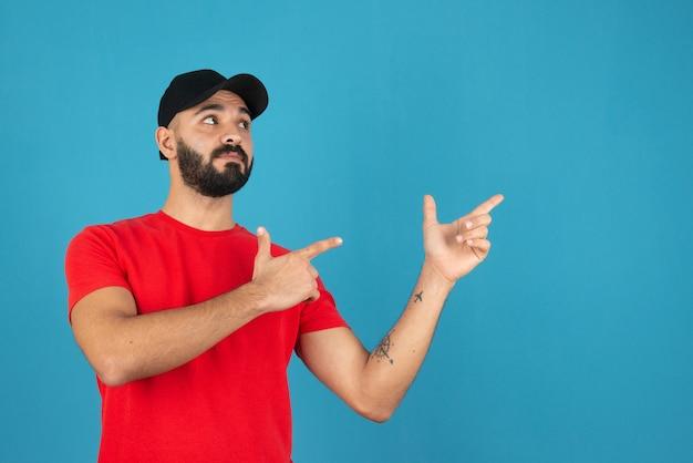 青い壁に向かって指しているハンサムな若い男。