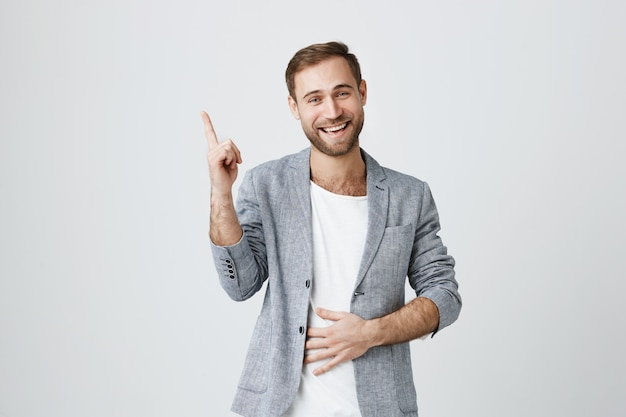 Красивый молодой человек, указывая пальцем на рекламу