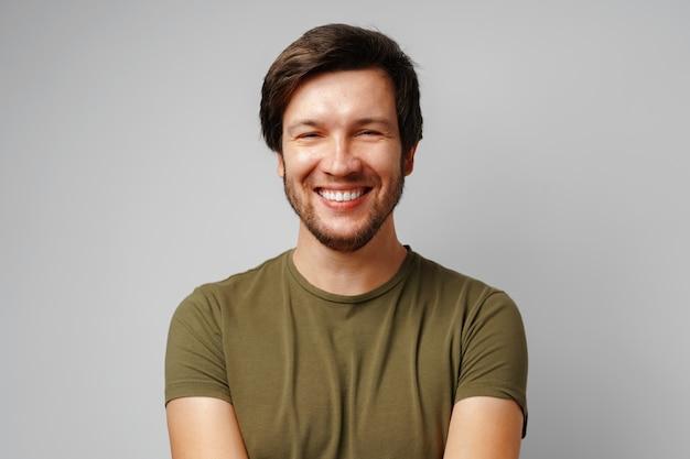 Красивый молодой человек портрет улыбается против серого