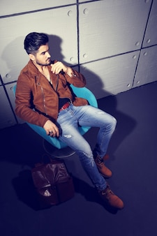 Handsome young man posing. jacket, boots, jeans, sunglasses.