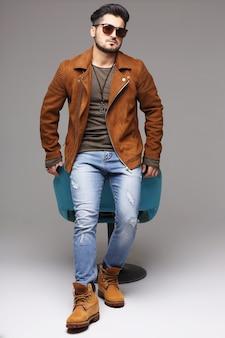 잘 생긴 젊은 남자 포즈. 재킷, 부츠, 청바지, 선글라스.