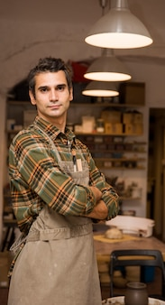 Handsome young man posing in pottery workshop