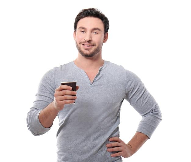 ハンサムな若い男がカップでポーズ