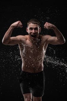 Handsome young man posing with water splashes on face and chest in studio shot
