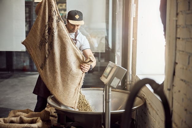 Handsome young man pouring unroasted coffee beans into metal hopper