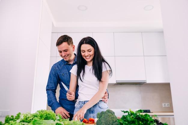 モダンなキッチンで思いやりのある愛情のある妻と週末に朝の朝食を準備しているハンサムな若い男、サラダのために新鮮な野菜を切る幸せな夫婦。