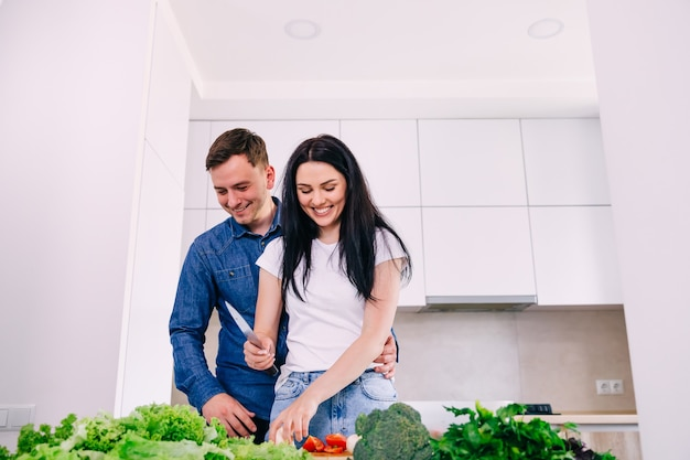 Handsome young man preparing morning breakfast on weekend with caring loving wife in modern kitchen, happy married couple cutting fresh vegetables for salad.