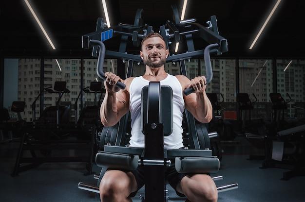 ハンサムな若い男は、特別な機械で彼の肩をポンプでくみます。フィットネスとボディービルのコンセプト。