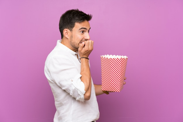 Handsome young man over purple  holding popcorns