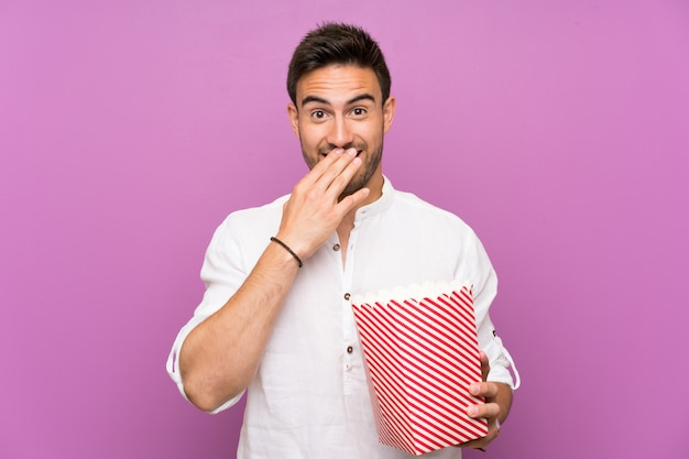Handsome young man over purple wall holding popcorns