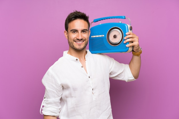 Handsome young man over purple wall holding a radio