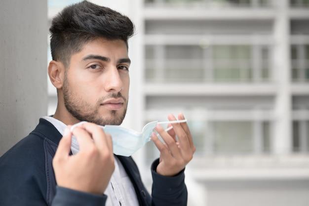 コロナウイルスから保護するためにサージカルマスクを身に着けているハンサムな若い男
